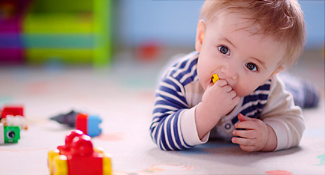bebê de 8 meses deitado no chão brincando. texto em destaque: Sinais de Autismo: Como identificá-los em bebês a partir de 8 meses!