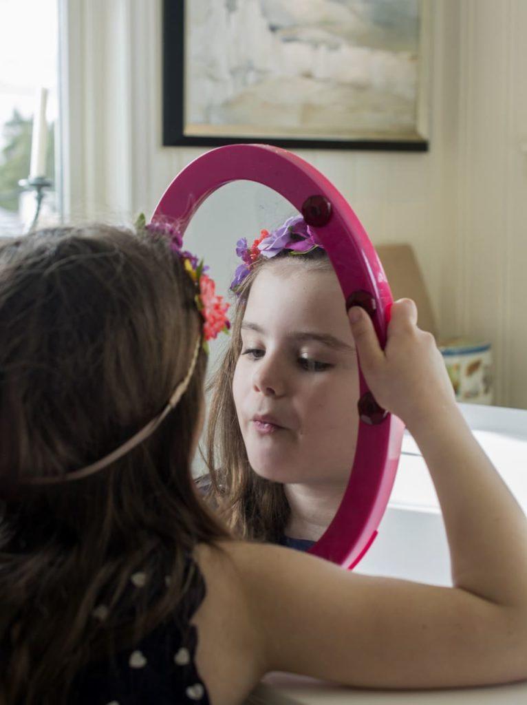 Menina se olhando no espelho. Texto em destaque: neurônios espelho!