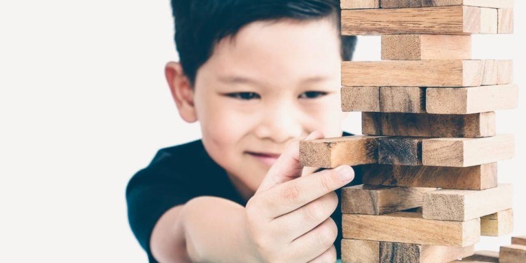 Menino brincando com peça de montar. Texto em destaque: Como a fonoaudiologia ajuda na TDAH infantil
