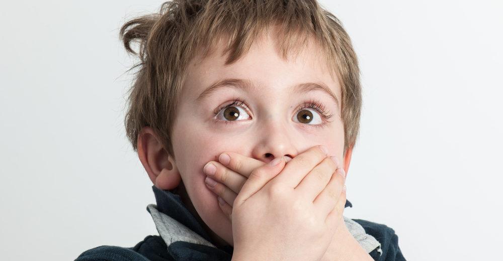 Menino com a mão na boca, representando a frustração de crianças que sofrem com gagueira infantil.